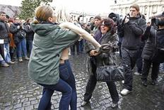 An activist (C) from women's rights protest group Femen is restrained by a policewoman (L) as a woman tries to hit her with an umbrella while Pope Benedict XVI leads his Angelus prayer from the window of his private apartment in Saint Peter's Square at the Vatican January 13, 2013. REUTERS/Giampiero Sposito