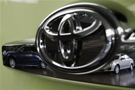 Toyota's Corolla Fielder (L) and Corolla Axio are reflected in a Toyota Forte's logo at the company's headquarters in Tokyo November 5, 2012. REUTERS/Kim Kyung-Hoon/Files