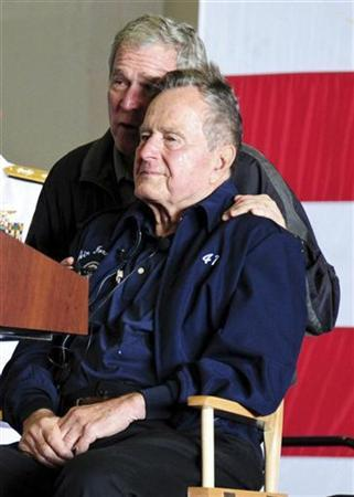 Former U.S. Presidents George W. Bush and his father George H.W. Bush attend a function onboard the USS George H.W. Bush aircraft carrier off the coast of Maine, June 10, 2012 in this U.S. Navy handout photo. The elder Bush, a former naval aviator, and his family members were attending a reenlistment ceremony on the carrier named for him. REUTERS/U.S. Navy/Handout