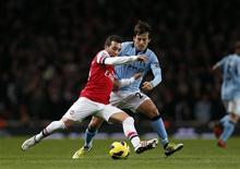 Duel entre David Silva de Manchester City (à droite) et Santi Cazorla à l'Emirates stadium. Les Citizens ont signé un net succès sur la pelouse de Arsenal (2-0), le premier en championnat en 38 ans. Manchester City est deuxième à sept points du leader United. /Photo prise le 13 janvier 2013/REUTERS/Eddie Keogh
