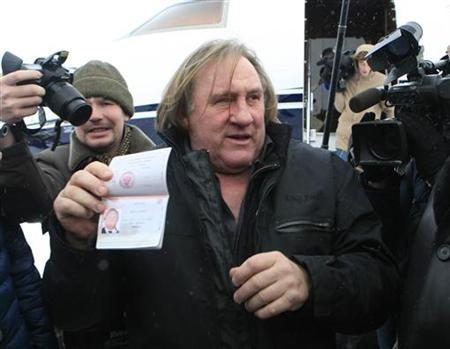 French film star Gerard Depardieu shows his passport after arriving at the airport in the town of Saransk in the Mordoviya Republic, southeast of Moscow, January 6, 2013. REUTERS/Yulia Chestnova
