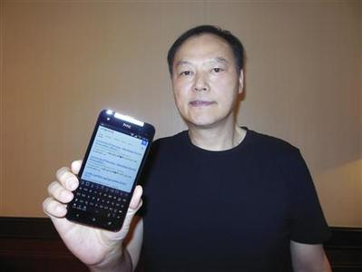 Peter Chou holds one of his devices sporting a new Myanmar font ahead of Monday's launch of the product in Yangon January 13, 2013. REUTERS/Jeremy Wagstaff