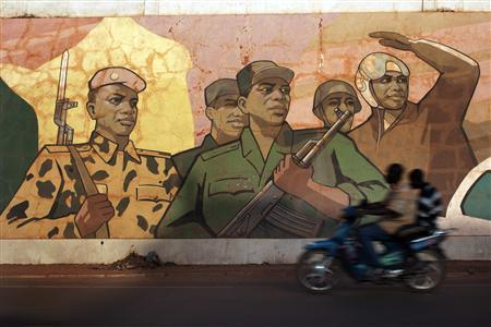 Motorcyclists drive past a mural showing Malian soldiers in the Malian capital of Bamako January 13, 2013. REUTERS/Joe Penney