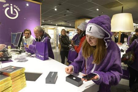 Alice, 18, who was in queue since 11 A.M. on September 26 and is one of the first customers to buy the iPhone5 in Sweden, holds the smartphone at a shop in central Stockholm early September 28, 2012. REUTERS/Bertil Enevag Ericson/Scanpix Sweden