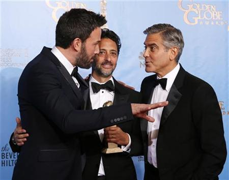 Producer and director Ben Affleck (L) talks with ''Argo'' producers Grant Heslov (C) and George Clooney after Affleck won Best Director and ''Argo'' won the award for Best Motion Picture Drama at the 70th annual Golden Globe Awards in Beverly Hills, California January 13, 2013. REUTERS/Lucy Nicholson