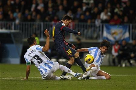 Barcelona's Lionel Messi (C) battles for the ball with Malaga's Weligton Robson (L) and Sergio Sanchez during their Spanish First Division soccer match at La Rosaleda stadium in Malaga, southern Spain January 13, 2013. REUTERS/Jon Nazca