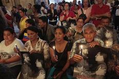 """La salud del presidente venezolano, Hugo Chávez, evoluciona """"favorablemente"""" a un mes de una compleja operación por cáncer, dijo el domingo el Gobierno, tras un fin de semana en el que varios líderes regionales y altos mandos de su gabinete lo visitaron en Cuba. En la imagen, decenas de personas participan en una misa, con velas e imágenes del presidente venezolano Hugo Chávez con el líder cubano Fidel Castro, en La Habana, el 12 de enero de 2013. REUTERS/"""