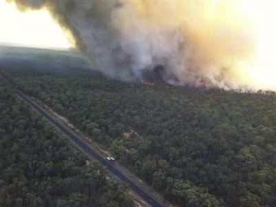 The Redbank North Fire burns close to the Newell Hwy near Coonabarabran, about 350km (217 miles) north west of Sydney, in this handout picture provided by the Rural Fire Service on January 14, 2013. REUTERS/NSW Rural Fire Service/Handout