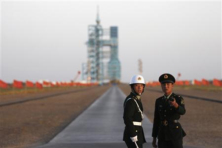 Soldiers stand in front of the Long March II-F rocket loaded with China's unmanned space module Tiangong-1 before its planned launch from the Jiuquan Satellite Launch Center, Gansu province in this September 29, 2011 file photo. REUTERS/Petar Kujundzic/Files