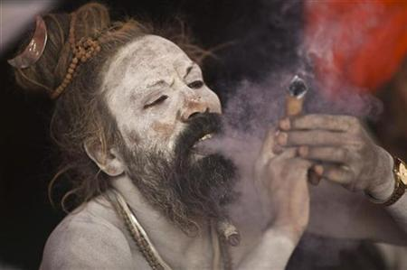 A Sadhu, or a Hindu holy man, smokes marijuana on a chillum on the banks of river Ganges ahead of the 'Kumbh Mela' (Pitcher Festival) in Allahabad January 11, 2013. REUTERS/Ahmad Masood