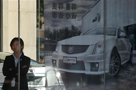 A woman stands next to a Cadillac CTS car poster outside a dealership in Beijing, October 31, 2012. REUTERS/Petar Kujundzic (CHINA - Tags: BUSINESS TRANSPORT)