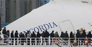 Parenti delle vittime su un traghetto di fronte alla Costa Concordia. Isola del Giglio, 13 gennaio 2013. REUTERS/Tony Gentile