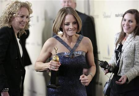 Actress Jodie Foster (C) runs with her Cecil B. DeMille Award at the Weinstein Company after party following the 70th annual Golden Globe Awards in Beverly Hills, California January 13, 2013. REUTERS/Jason Redmond