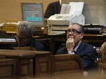El Ibex-35 abrió el lunes con nuevas ganancias, extendiendo la racha alcista registrada desde el arranque del año (+6,1 por ciento) al disminuir la aversión de los inversores a los activos de los países periféricos de la eurozona. En la imagen, dos hombres en la bolsa de Madrid en una fotografía de archivo de abril de 2012. REUTERS/Andrea Comas