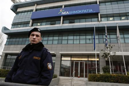 A policeman stands guard in front of headquarters of co-ruling New Democracy party after an attack in Athens January 14, 2013. Unknown assailants fired shots at the headquarters of Greece's New Democracy party in the early hours of Monday, causing minor damage to the building but no injuries, police said. Officials said it was a symbolic attack against Prime Minister Antonis Samaras, who no longer uses his office on Syngrou Avenue near the centre of Athens. The assault followed a barrage of makeshift bomb attacks against journalists and political targets in recent days. REUTERS/Yorgos Karahalis