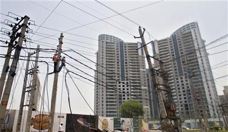 Employees from the electricity board work on overhead cables installed in front of the residential apartments constructed by Indian property developer DLF at Gurgaon, on the outskirts of New Delhi, June 19, 2012. REUTERS/Parivartan Sharma/Files