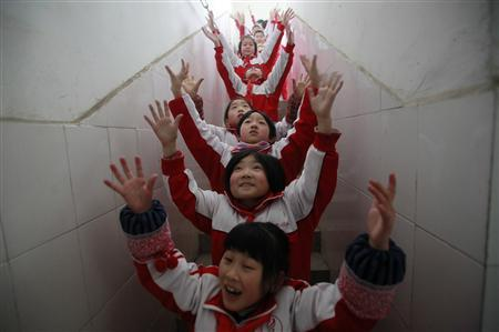 Students do body exercise during class break in a classroom building on a foggy day in Jinan, Shandong province, January 14, 2013. Heavy fog enveloped a large swathe of east and central China, with the city's residents being advised to stay indoors to avoid the heavily polluted air, Xinhua News Agency reported. REUTERS/China Daily
