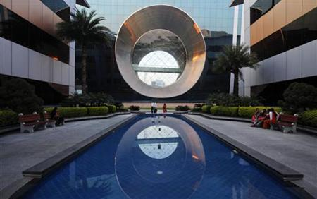 Employees walk in front of a building dubbed the 'washing machine', a well-known landmark built by Infosys at the Electronics City IT district in Bangalore, February 28, 2012. REUTERS/Vivek Prakash/Files