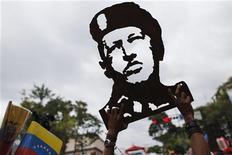 Apoiador do presidente venezuelano, Hugo Chávez, segura imagem esculpida em madeira durante manifestação diante do Palácio Miraflores, em Caracas. A infecção pulmonar que acometeu o presidente venezuelano, Hugo Chávez, foi controlada e sua condição clínica está melhorando, mais de um mês após ter passado pela quarta cirurgia contra o câncer em Cuba, informou o governo da Venezuela. 10/01/2013 REUTERS/Jorge Silva