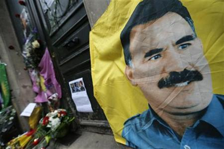 A flag with the portrait of jailed Kurdistan Workers Party (PKK) leader Abdullah Ocalan is seen in front of the entrance of the Information Centre of Kurdistan in Paris, where three Kurdish women were found shot dead, January 11, 2013. REUTERS/Christian Hartmann