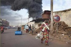 Market vendors carry their wares away from a fire at Ngolonina market in the Malian capital of Bamako, January 12, 2013.The fire was started after an accident at a gasoline depot. REUTERS/Joe Penney (MALI - Tags: DISASTER)