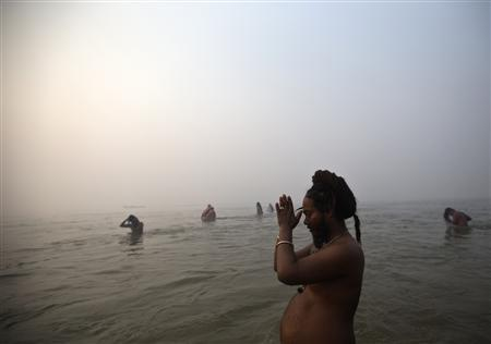 A Sadhu or a Hindu holy man prays as he takes a dip during the first ''Shahi Snan'' (grand bath) at the ongoing ''Kumbh Mela'', or Pitcher Festival, in the northern Indian city of Allahabad January 14, 2013. REUTERS/Ahmad Masood