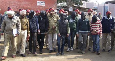 Six men with their faces covered, accused of a gang rape in Punjab are escorted by police to a court at Gurdaspur in Punjab January 13, 2013. REUTERS/Stringer