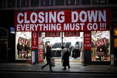 La previsión de crecimiento para la mayoría de los países industrializados está mejorando, liderado por Estados Unidos y Reino Unido, al tiempo que las economías de China e India han alcanzado puntos de inflexión positivos, dijo el lunes la Organización para la Cooperación y el Desarrollo Económico. En la imagen del 5 de diciembre se ve a unas personas pasando ante una tienda en el centro de Londres que anuncia rebajas antes de cerrar. REUTERS/Andrew Winning