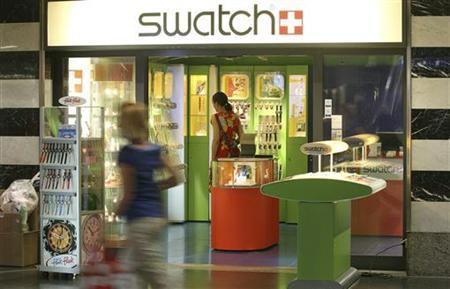 A woman looks at watches at a Swatch store at Zurich central station July 24, 2012. REUTERS/Arnd Wiegmann (SWITZERLAND - Tags: BUSINESS)