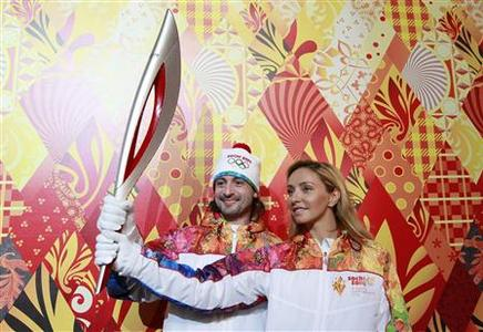 Russian ice dancers Tatyana Navka (R) and Ilya Averbukh hold the Olympic torch for the Sochi 2014 Winter Olympics during a presentation ceremony in Moscow January 14, 2013. REUTERS/Maxim Shemetov