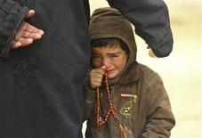 A boy, standing next to his father, cries as they wait to receive humanitarian aid in the countryside of Idlib January 13, 2013. Picture taken January 13, 2013. REUTERS/Giath Taha