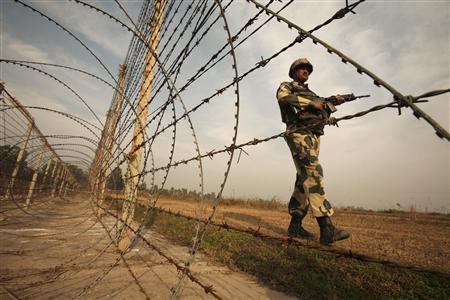 An Indian Border Security Force (BSF) soldier patrols near the fenced border with Pakistan in Suchetgarh, southwest of Jammu January 14, 2013. India's army chief General Bikram Singh held out the threat of retaliating against Pakistan for the killing of two soldiers at the de facto border in Kashmir, saying he had asked his ground commanders to be aggressive in the face of provocation. REUTERS/Mukesh Gupta