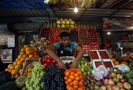 A man arranges fruits at his stall at a wholesale market in Mumbai, January 14, 2013. REUTERS/Vivek Prakash