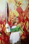 Los organizadores de los Juegos Olímpicos de invierno de Sochi 2014 presentaron el lunes una antorcha futurista basada en los contrastes del país más grande del mundo y que combina el folclore ruso - incluyendo el mítico Pájaro de Fuego - con la tecnología de la era espacial. En la imagen, la patinadora rusa Tatyana Navka sostiene la antorcha olímpica de los Juegos de Invierno de Sochi 2014 durante su ceremonia de presentación, en Moscú, el 14 de enero de 2013. REUTERS/Maxim Shemetov