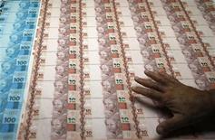 Imagen de archivo de un trabajador revisando hojas de billetes en la Casa da Moeda do Brazil (la casa de moneda) en Río de Janeiro, ago 23 2012. Economistas redujeron sus pronósticos para la expansión económica de Brasil este año a un 3,20 por ciento desde un 3,26 por ciento, mostró el lunes el sondeo semanal que realiza el banco central. REUTERS/Sergio Moraes