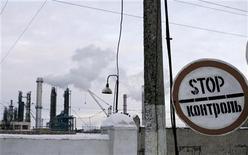 Знак остановки за территорией потребляющего природный газ химкомбината STIROL в Горловке, Украина 9 января 2009 года. Ищущая новых займов Украина нашла еще $1 миллиард на поддержку государственного Нафтогаза, тогда как размышляющий над возобновлением кредитов МВФ советовал повысить тарифы монопольного поставщика газа населению ради залатывания дыр в казне. REUTERS/Valery Belokryl