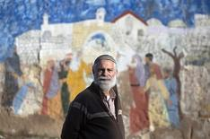 David Wilder, a spokesman for the Jewish Community of Hebron, poses in front of a biblical-themed mural in the West Bank city of Hebron January 13, 2013. Entrenched in what they view as their Biblical heartland, the hardline Jewish settlers of Hebron look forward with delight to next week's Israeli election. Picture taken January 13, 2013. REUTERS/Baz Ratner