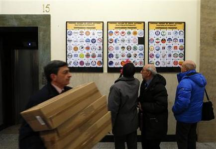 Italy's Interior Ministry employees stand near electoral logos to be used in next month's elections in Rome January 14, 2013. REUTERS/ Alessandro Bianchi