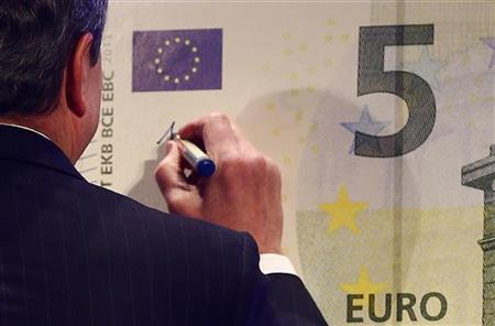 Mario Draghi, President of the European Central Bank (ECB), signs an oversized new unveiled 5 euro note in Frankfurt, January 10, 2013. REUTERS/Kai Pfaffenbach (GERMANY - Tags: BUSINESS)