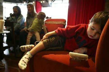 Matthew West, 3, watches a video on his Mom's iPhone while she talks with friends at Starbucks' Roy Street Coffee and Tea in Seattle, Washington, March 25, 2010. REUTERS/Marcus Donner/Files