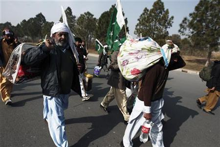 Supporters of Muhammad Tahirul Qadri, leader of Mihaj-ul-Quran, carry their belongings as they arrive to take part in a protest in Islamabad January 14, 2013. REUTERS/Zohra Bensemra