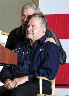 Former U.S. Presidents George W. Bush and his father George H.W. Bush attend a function onboard the USS George H.W. Bush aircraft carrier off the coast of Maine, June 10, 2012 in this U.S. Navy handout photo. REUTERS/U.S. Navy/Handout