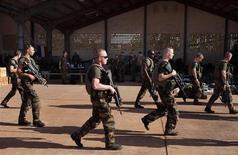 Francia tiene previsto aumentar el número de efectivos en Mali en los próximos días a 2.500 militares y está trabajando para acelerar el despliegue de tropas de países del oeste africano en una operación contra rebeldes islamistas, según dijo el lunes el Gobierno galo. En la imagen, soldados franceses pasan junto a un hangar en la base aérea del Ejército maliense en Bamako, el 14 de enero de 2013. REUTERS/Joe Penney