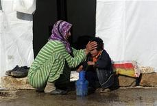 Um refugiado sírio limpa o rosto de um garoto no exterior de uma tenda em Azaz, na Síria. 13/01/2013 REUTERS/Muzaffar Salman