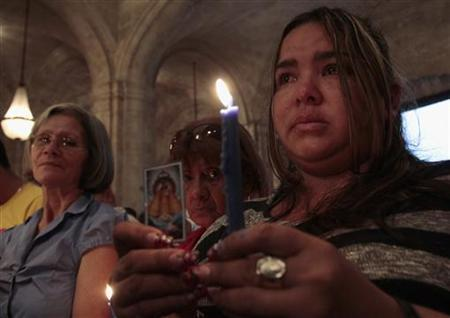 A woman holds a candle during a mass to pray for the recovery of Venezuela's President Hugo Chavez in Havana January 12, 2013. REUTERS/STRINGER