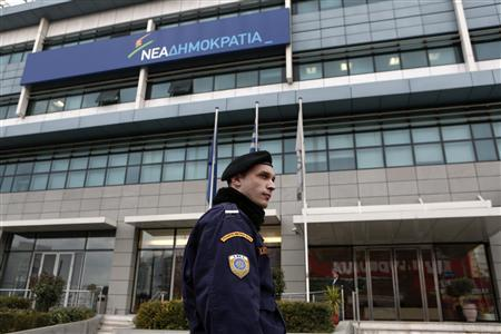 A policeman stands guard in front of the headquarters of co-ruling New Democracy party after an attack in Athens January 14, 2013. Unknown assailants fired shots at the headquarters of Greece's New Democracy party in the early hours of Monday, causing minor damage to the building but no injuries, police said. Officials said it was a symbolic attack against Prime Minister Antonis Samaras, who no longer uses his office on Syngrou Avenue near the centre of Athens. The assault followed a barrage of makeshift bomb attacks against journalists and political targets in recent days. REUTERS/Yorgos Karahalis