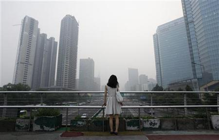 A woman stands on an overhead bridge on a hazy day in Beijing's central business district July 28, 2012. REUTERS/Jason Lee/Files