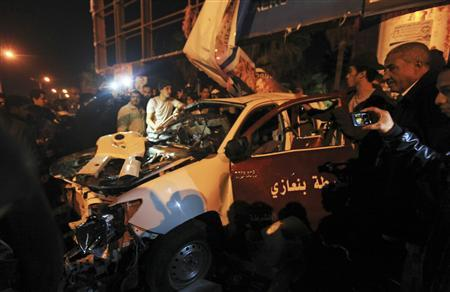People look at the wreckage of a police car after an attack, in Benghazi January 14, 2013. REUTERS/Esam Al-Fetori