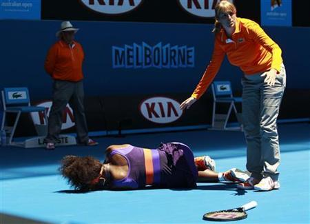 An offical stands over Serena Williams of the U.S. after she fell over during their women's singles match at the Australian Open tennis tournament in Melbourne, January 15, 2013. REUTERS/Daniel Munoz