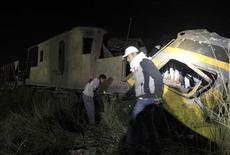 People walk around the wreckage of a military train crash in the Giza neighbourhood of Badrashin, about 40 km (25 miles) west of Cairo January 15, 2013. A military train carrying young recruits to army camp derailed in a Cairo suburb on Tuesday, killing 17 people and injuring 103, Egypt's health ministry spokesman said. REUTERS/Mohamed Abd El Ghany (EGYPT - Tags: TRANSPORT DISASTER MILITARY)